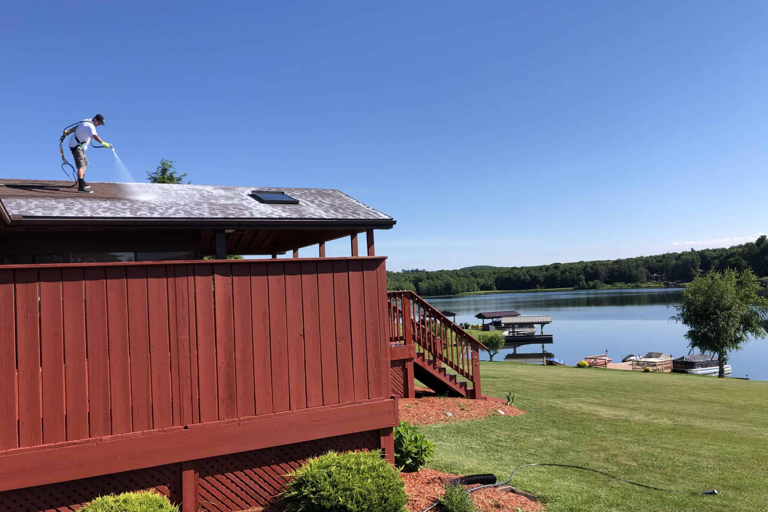 Tech Spraying Roof of Lake House